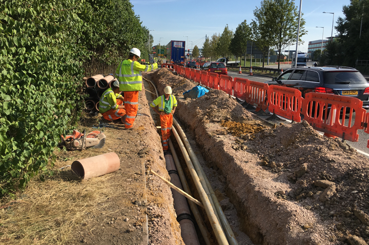Contractors laying roadside cables for a utilities project